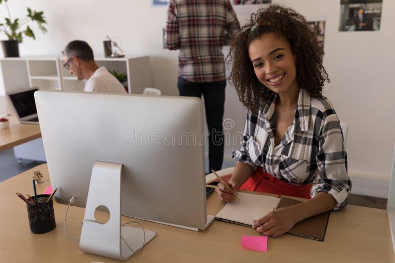 Żeński wykonawczy pisać na dzienniczku przy biurkiem zdjęcie stock