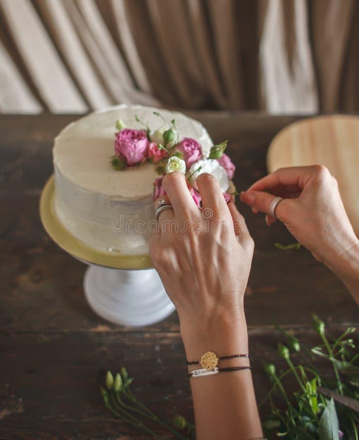 Żeńskie ręki dekoruje białego śmietanka tort obraz stock