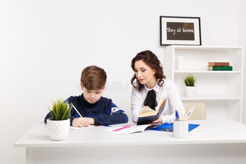 Żeńskiego nauczyciela pomocy nastoletnia chłopiec robić jego pracie domowej Robić pracie domowej wpólnie zdjęcia stock