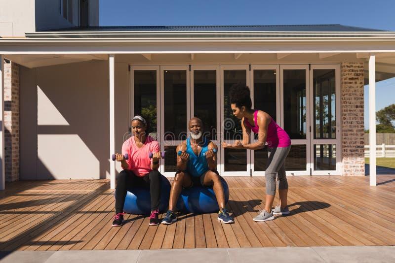 Żeńskiego trenera stażowa starsza para w równoważenia ćwiczeniu w podwórko obraz stock