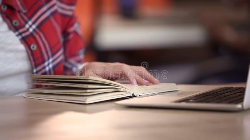 Żeńskiego ucznia czytelnicza książka, robi pracie domowej przy laptopu komputerem osobistym w bibliotece, edukacja obraz royalty free