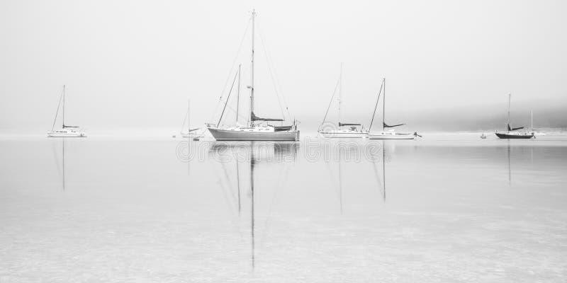 Żeglowanie łodzie na mglistym jeziorze zdjęcia stock