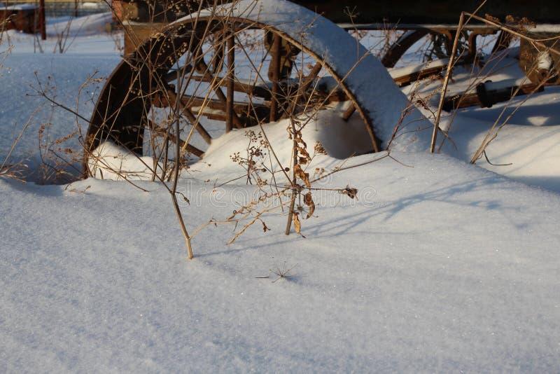 Żelazna stara ośniedziała koło fura wtykająca w śnieżnej furze zdjęcie stock