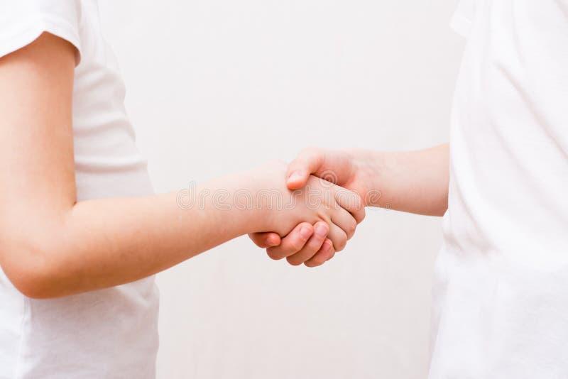 当他们见面时,两个孩子握手 图库摄影