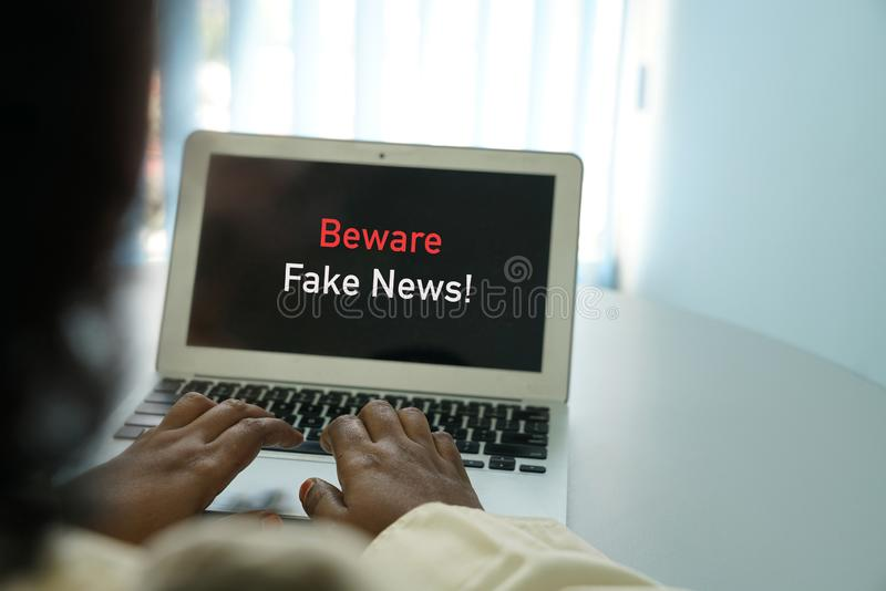 当心假新闻概念:浏览膝上型计算机的手互联网 免版税库存图片