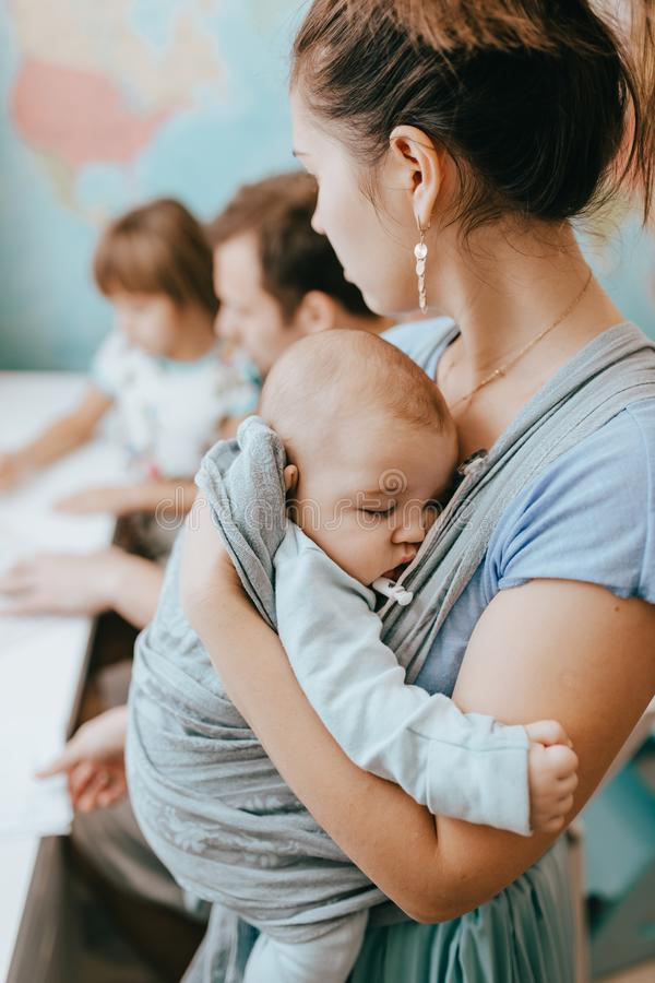 当父亲在有地图的屋子里帮助他的小女儿做教训在书桌在时,母亲抱着一个婴孩 库存图片