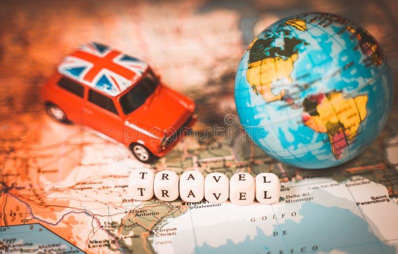 微型玩具葡萄酒汽车、一个世界地图气球和旅行词在地图 旅行和运输概念 免版税库存照片