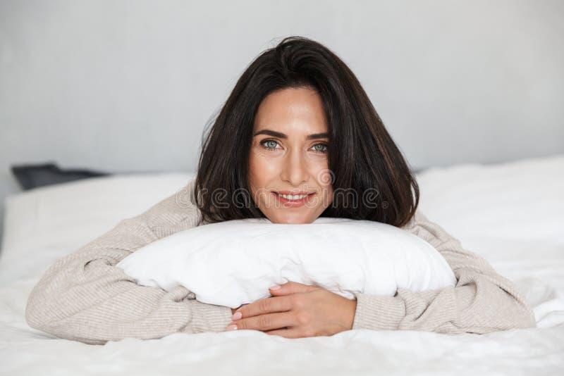 微笑中年的妇女30s照片,当在家时在与白色亚麻布的床上 库存照片