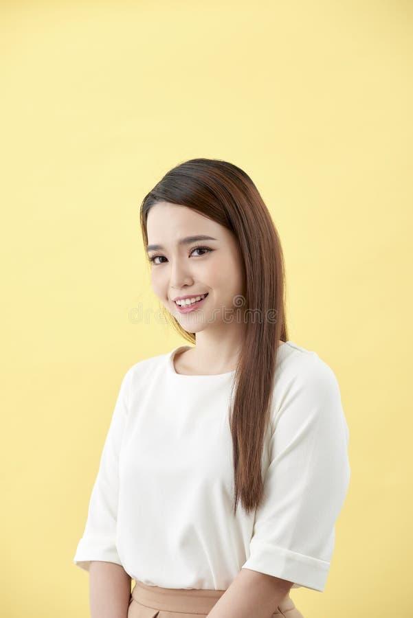 微笑与笑涡在黄色背景的长发黑眼圈的亚裔妇女 免版税图库摄影