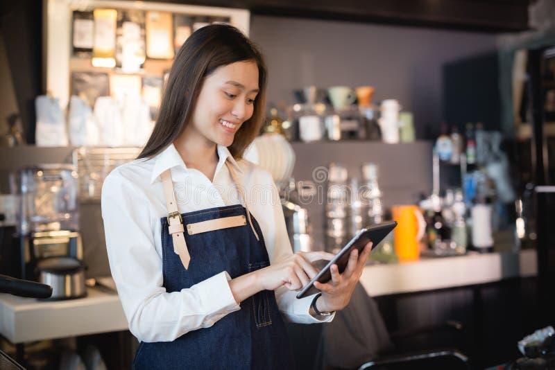 微笑与片剂的亚洲妇女barista在她的手上,女性雇员接受从网上顾客的命令 免版税图库摄影