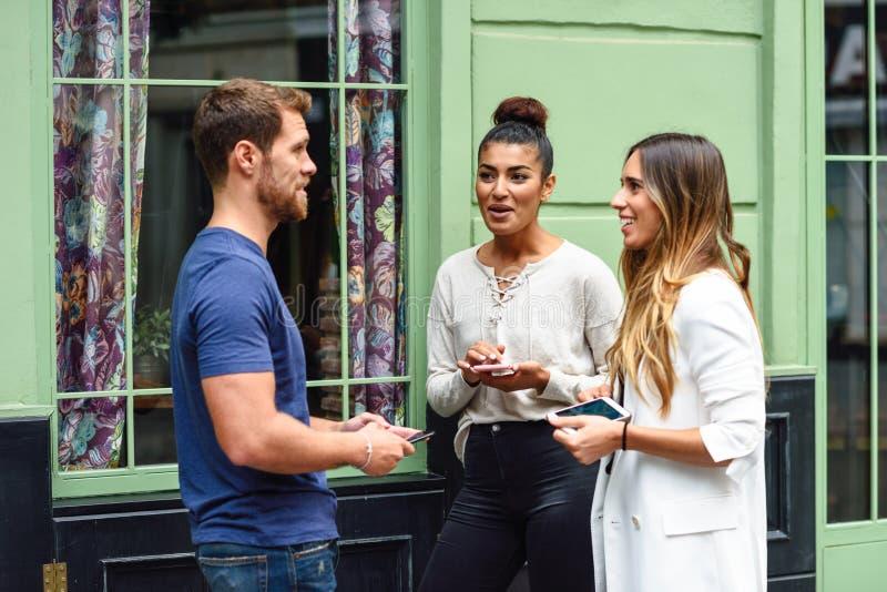 微笑三个不同种族的人的朋友谈话和户外 库存图片