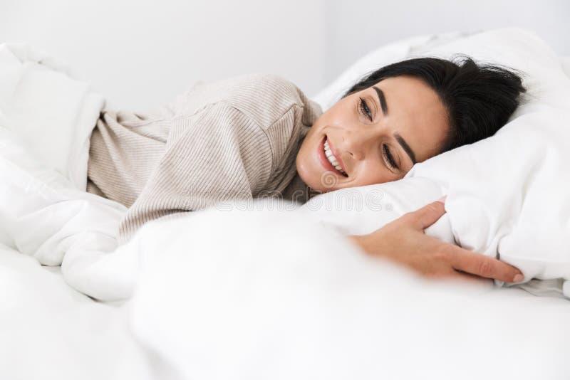 微笑可爱的妇女30s照片,当在家时在与白色亚麻布的床上 库存照片