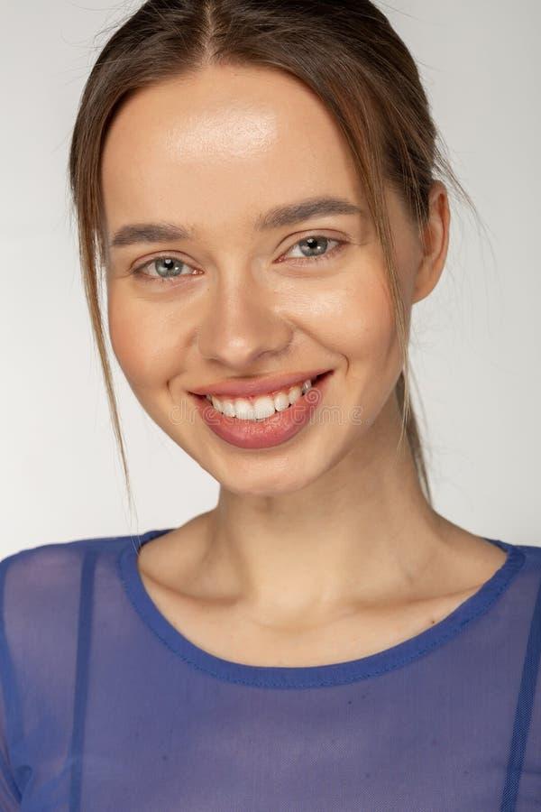微笑对照相机的年轻美丽的逗人喜爱的快乐的女孩画象  免版税库存图片