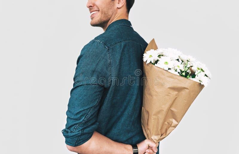 微笑年轻愉快的人的背面图图象掩藏白花花束  与一束花的有吸引力的男性模型 免版税库存图片