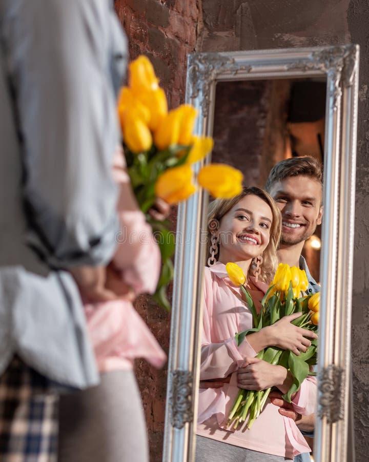 微笑快乐的放光的夫妇,当调查镜子时 免版税库存图片
