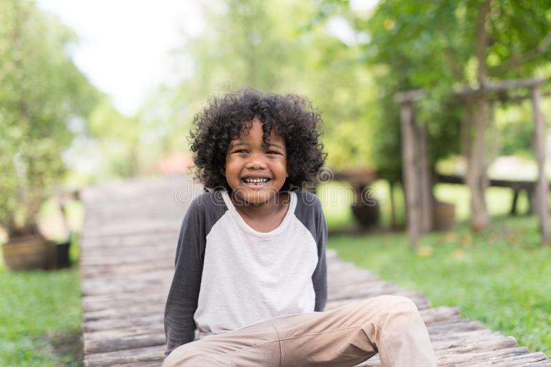 微笑在自然公园的一个逗人喜爱的非裔美国人的小男孩的画象 库存照片