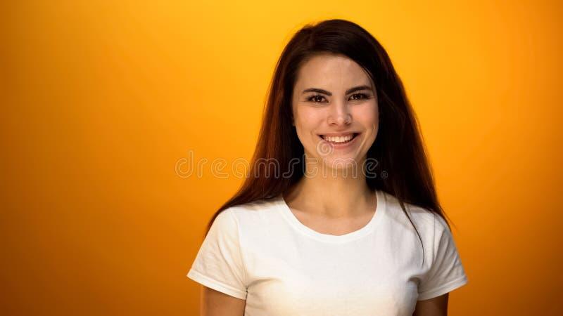 微笑在黄色背景的美女,健康和对生活满意 免版税库存图片