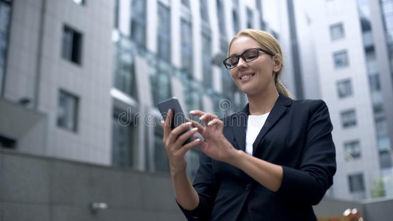 微笑办公室的夫人发短信与男朋友和,聊天在应用程序,约会网站 免版税库存照片
