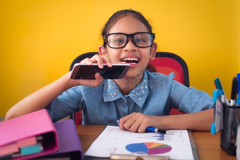 微笑充满幸福的逗人喜爱的女孩戴着眼镜隔绝在黄色背景 图库摄影