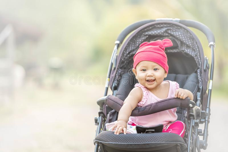 微笑和查寻对照相机的婴孩可爱的女孩户外 美丽的亚洲人6个月婴儿有幸福时光在Th公园 免版税库存照片