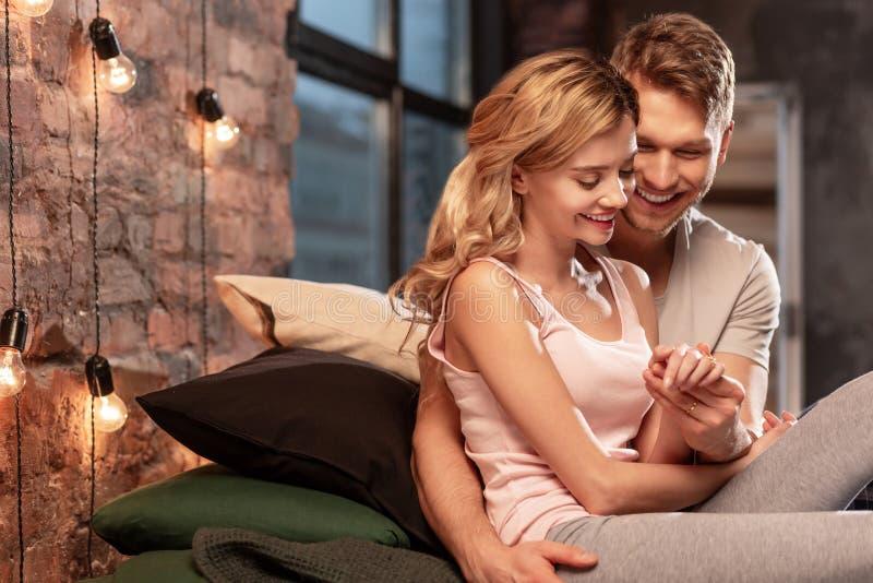 微笑和接触他可爱的妇女的手的爱的丈夫 免版税库存照片