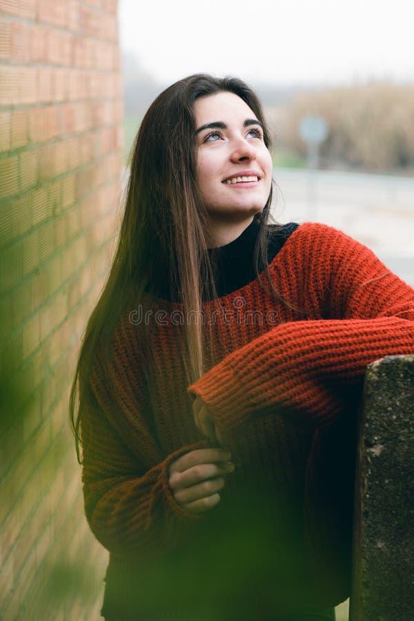 微笑和接触她的头发的年轻俏丽和愉快的女孩 户外方式纵向 免版税库存照片