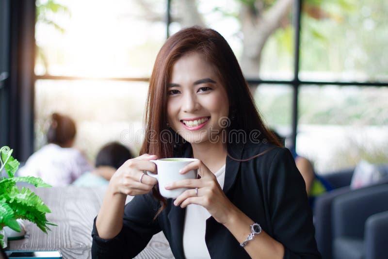 微笑和拿着喝的亚裔女商人杯子咖啡在咖啡咖啡馆 免版税库存照片