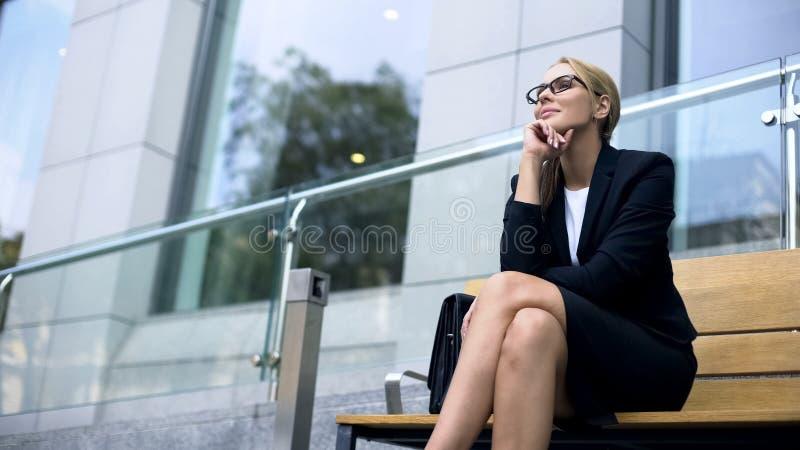 微笑愉快的女实业家坐长凳和,招呼新的天,喜爱的工作 免版税库存图片