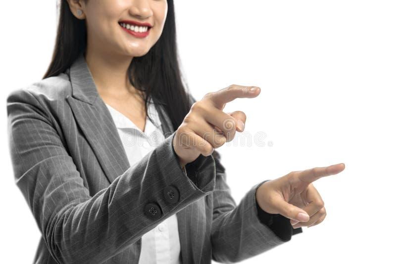 微笑的亚洲女商人接触某事用她的两只手指手 免版税库存照片
