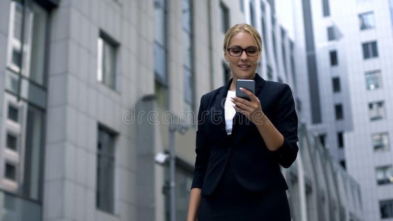 微笑的企业夫人在品牌商店收到了在智能手机的消息关于折扣 库存图片
