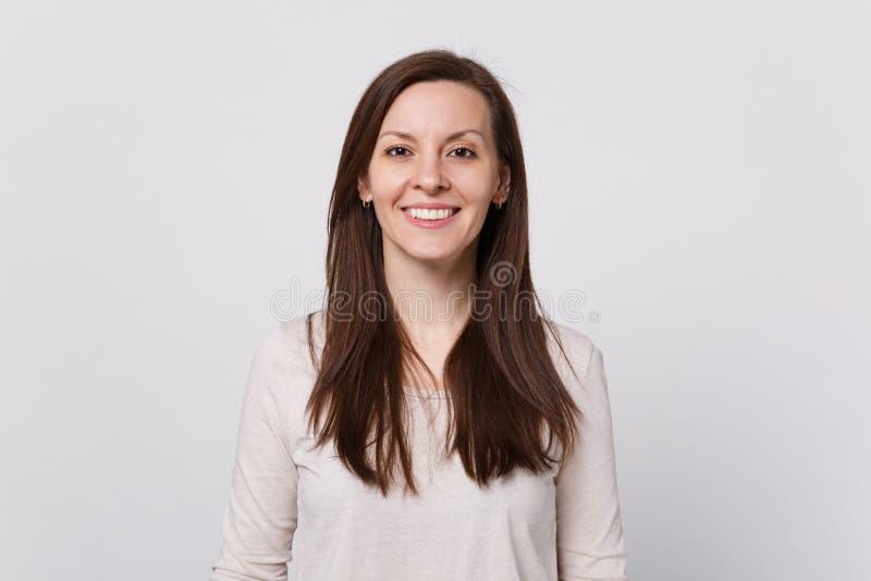 微笑的可爱的年轻女人画象站立和看照相机的轻的衣裳的隔绝在白色墙壁背景  库存照片