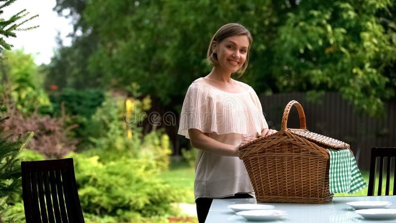 微笑的夫人在桌,家庭晚餐户外,野餐准备上把篮放 免版税库存照片