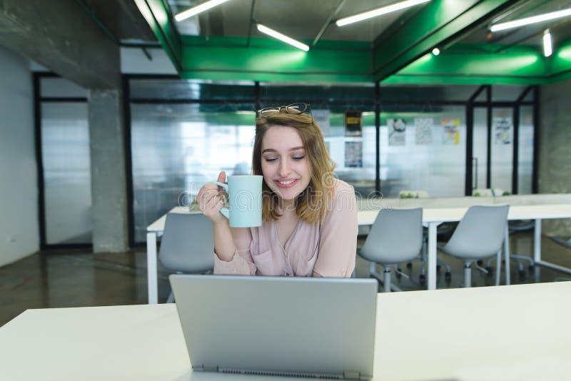 微笑的女孩,有一杯咖啡的一个办公室工作者在他的坐在桌上和运转在膝上型计算机的胳膊的 图库摄影
