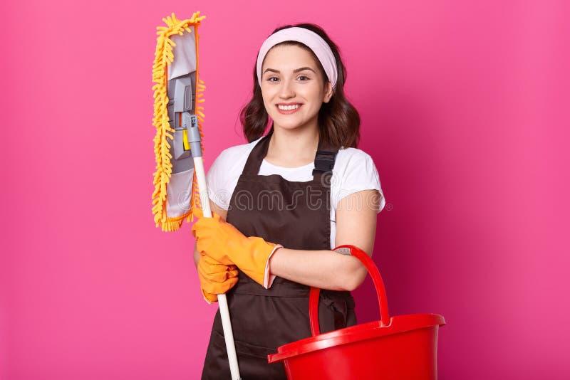 微笑的女性佩带棕色围裙,并且黄色橡胶手套,拿着拖把和红色桶 年轻女人清洗房子 美女 免版税图库摄影