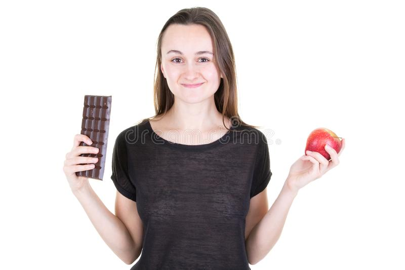 微笑的妇女用健康苹果和不健康的食物巧克力块在困难的选择 库存照片