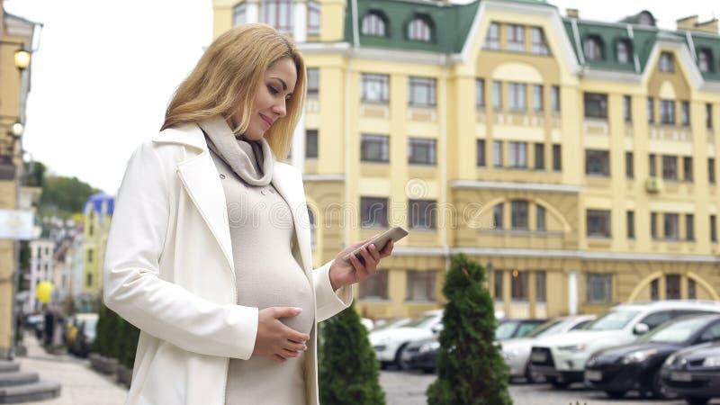 微笑的孕妇读书电话留言,分娩应用,作梦 库存照片