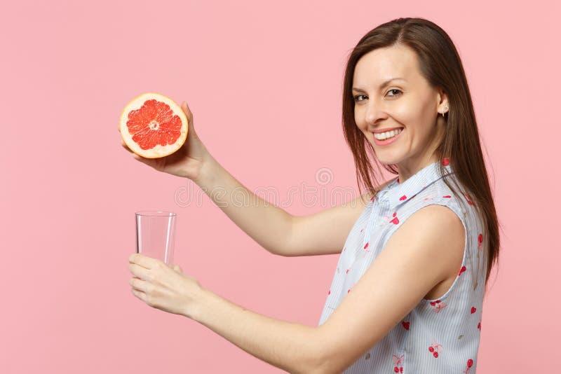 微笑的少女侧视图举行一半新鲜的成熟葡萄柚玻璃杯子的夏天衣裳的隔绝在桃红色 免版税库存图片