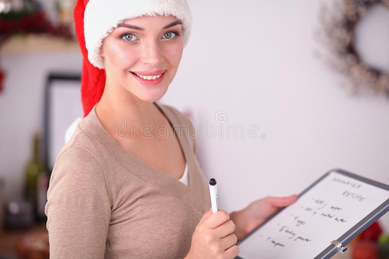 微笑的少妇在厨房里,隔绝在圣诞节背景 免版税库存照片