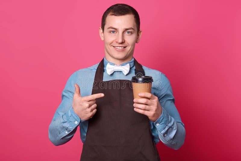 微笑的年轻人侍者在餐馆工作,建议喝从一次性杯子,在芳香饮料的点的咖啡,佩带 免版税库存图片