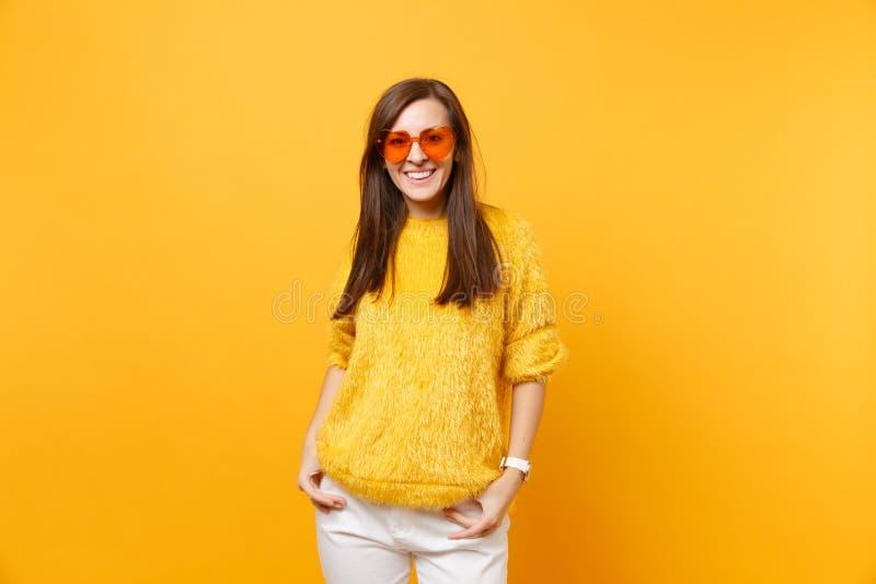 微笑的年轻女人画象毛皮毛线衣的,站立在口袋的心脏橙色玻璃kepping的手隔绝在明亮 免版税库存图片