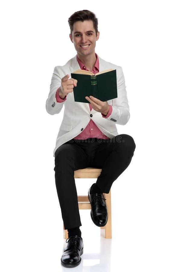微笑的聪明偶然人读书和指向手指,当坐时 免版税库存图片