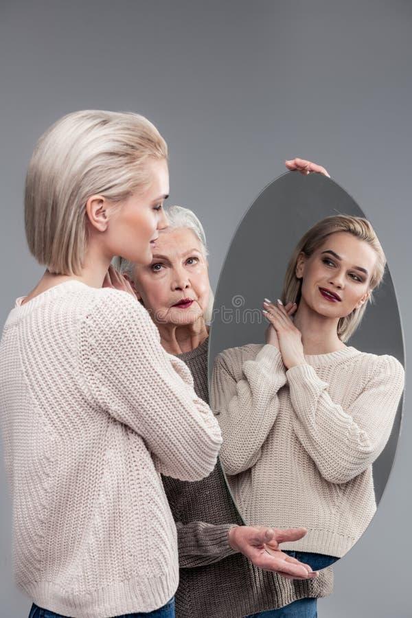 微笑白肤金发的少女,当看在圆的镜子时 库存图片