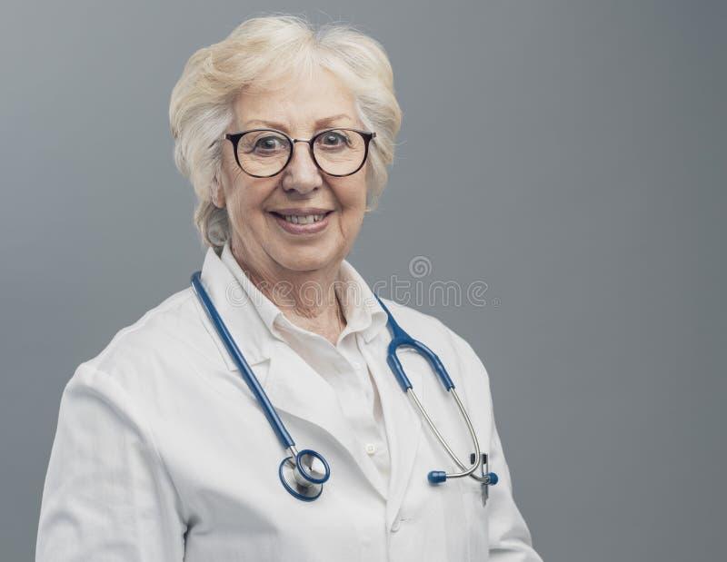 微笑资深女性的医生摆在和 库存图片