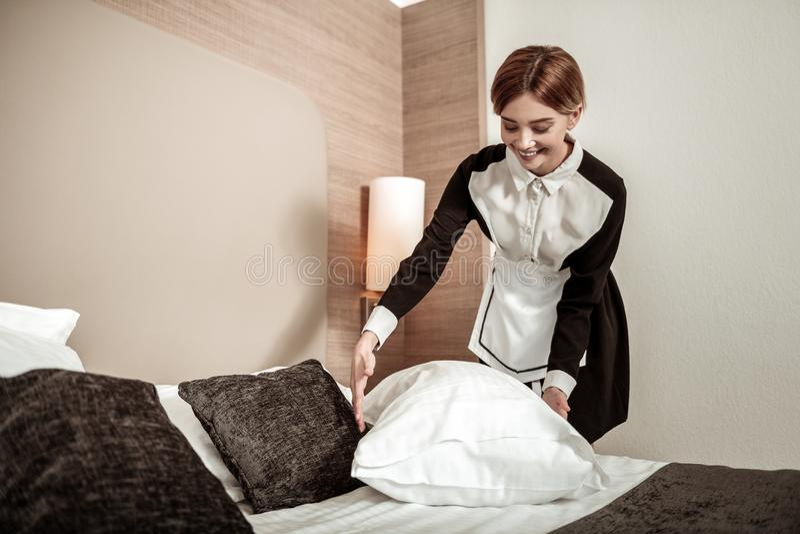微笑金发的旅馆的佣人,当做床客户时 免版税图库摄影