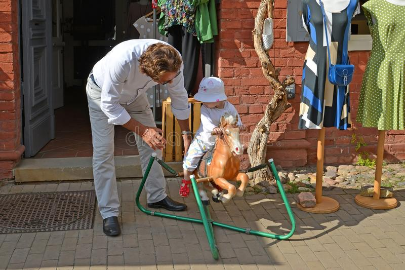德国波茨坦 人在玩具马滚动小孩子 库存图片
