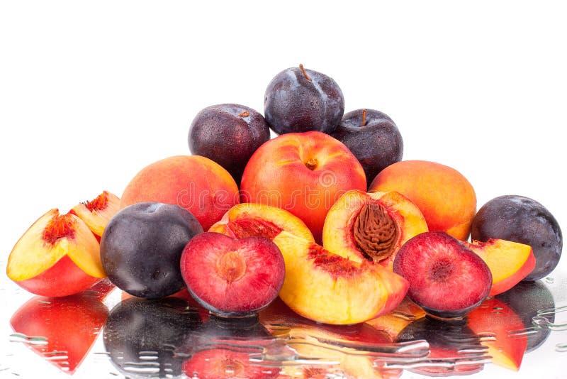很多明亮的果子、整个和裁减桃子和李子在镜子白色背景在水中落下隔绝 免版税库存图片