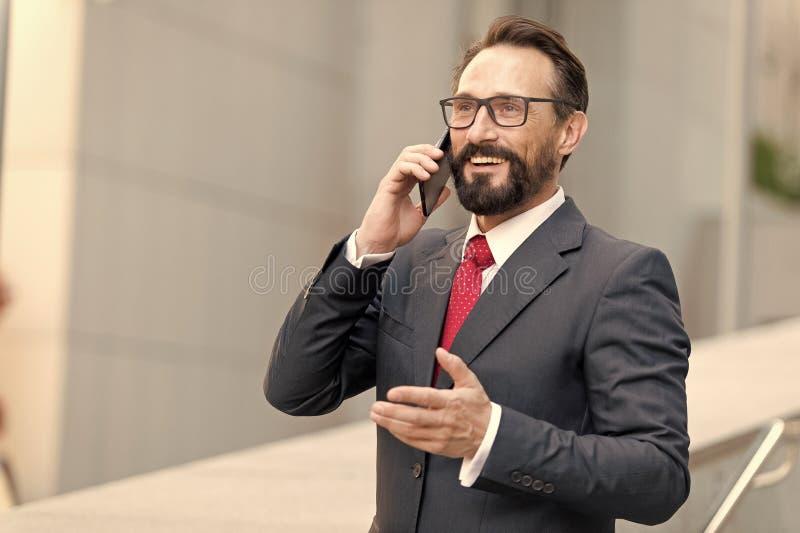 很多!有胡子的商人由电话讲话并且笑 观点的玻璃的一个年轻可爱的商人使用智能手机 库存图片