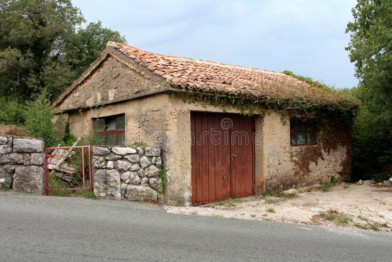 很少使用了与生锈的金属门和小窗口的老车库部分地长满与履带牵引装置植物在石墙旁边和 免版税图库摄影