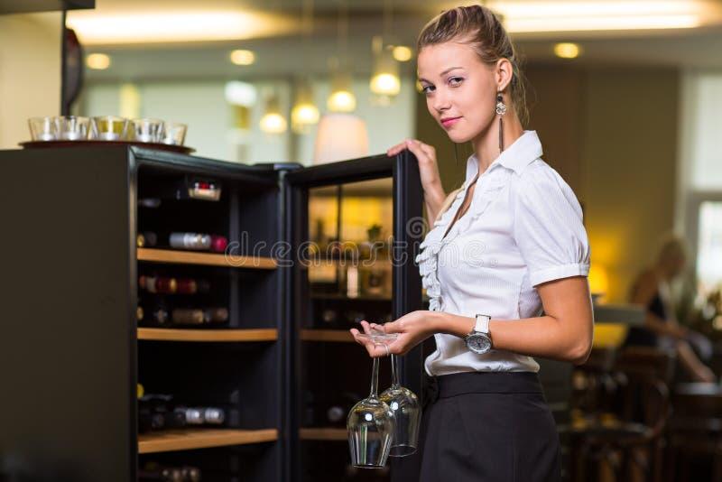 得到一个瓶客人的美味的酒的逗人喜爱的女服务员 库存照片