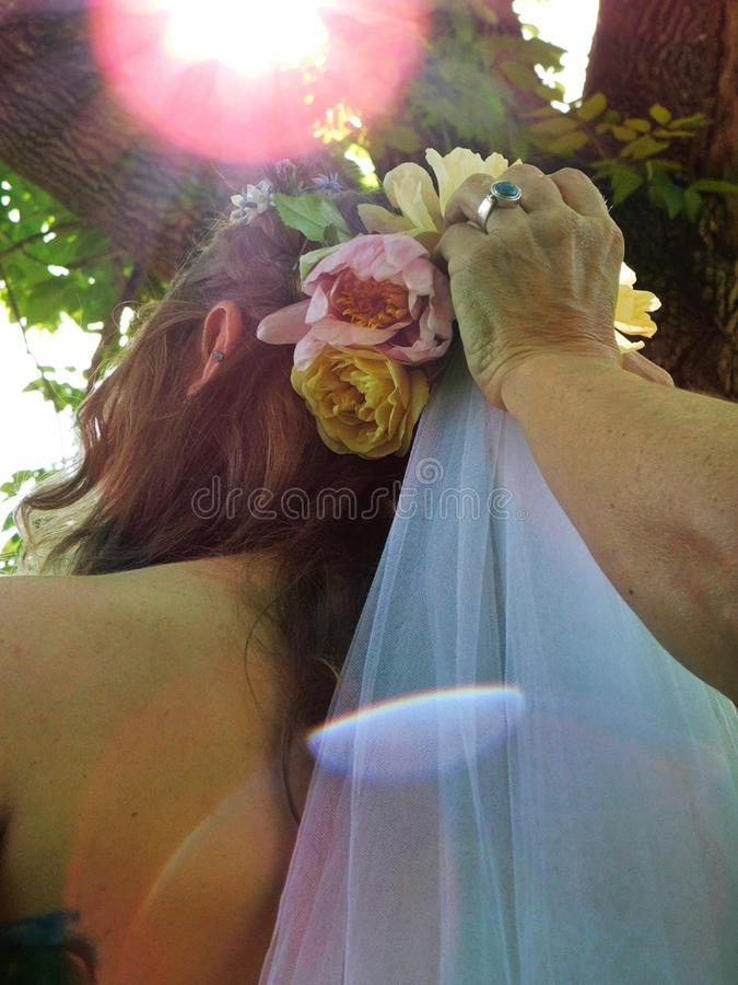 得到她的面纱的新娘被调整在她的室外婚礼 库存照片